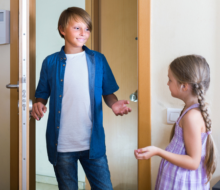 expected: Hospitable russian child receiving expected friend at home interior. focus on boy Stock Photo