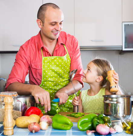 healthy cooking: Portrait of smiling dad and little daughter cooking