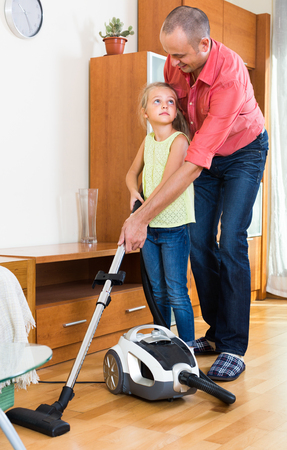 cleanup: Little girl helping father to do regular clean-up indoors
