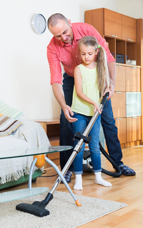 cleanup: european girl helping father to do regular clean-up indoors