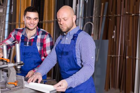 toolroom: Two joyful smiling workmen in uniform working on a machine in PVC shop