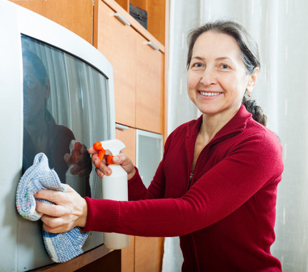 tele: Smiling mature woman wiping the dust  on TV at home Stock Photo