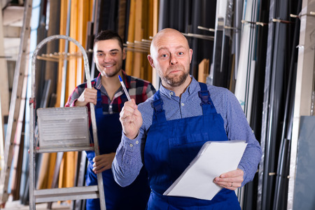 enginery: Two cheerful production workers in coverall with different PVC window