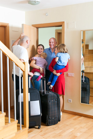 come home: Happy family with kids seeing off the relatives to home