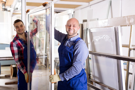 cheerful workmen with windows production at modern factory