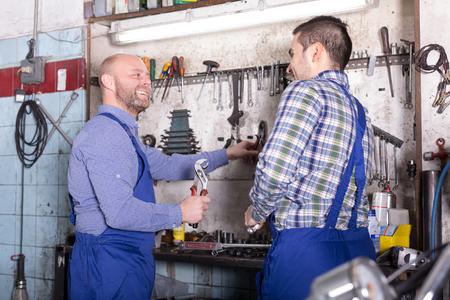 journeyman: Two positive mechanics working at the workshop Stock Photo
