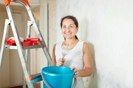 priming paint: Mature woman makes repairs in the apartment
