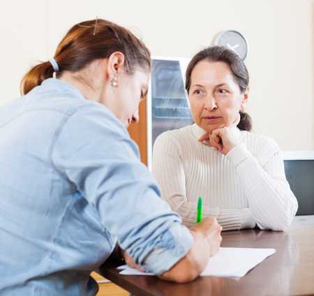 outreach: Mature woman answer questions of outreach worker with paper in home or office
