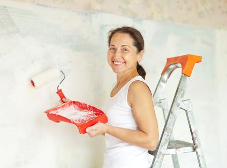 priming brush: Happy mature woman makes repairs at home