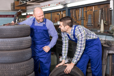 mounting holes: Cheerful adult mounting specialists working at auto repair shop. Focus on the right man