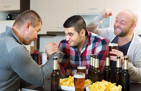 borracho: Dos amigos sonrientes macho adultas armwrestling en la mesa con cerveza y patatas fritas