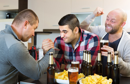drunk: Two smiling adult male friends armwrestling at the table with beer and chips