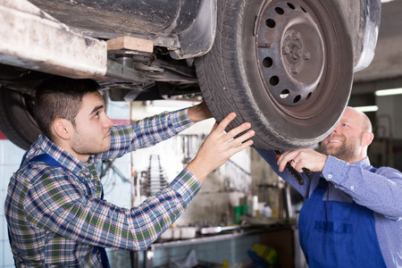 mounting holes: Positive workers fixing car tire leak Stock Photo
