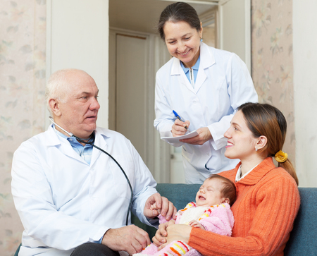 children's doctor: pediatrician doctor examining newborn baby on mothers arms in house. Mature nurse writes symptoms Stock Photo