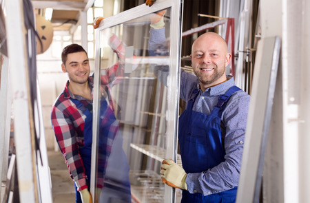 thermoplastic: Couple of workmen  in uniform  inspecting windows at workshop Stock Photo
