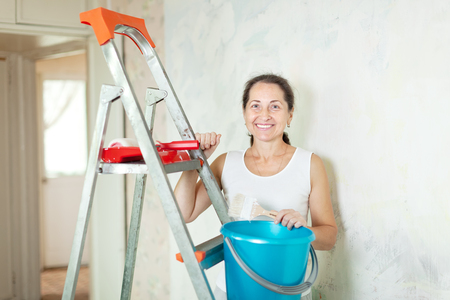 priming brush: Mature woman makes repairs at home
