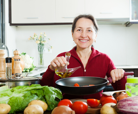 fryingpan: Happy mature woman pouring oil into fryingpan at home Stock Photo