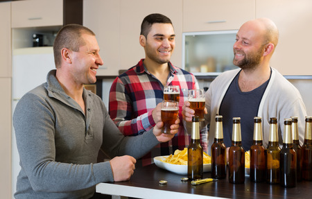 bout: Three smiling male friends with glasses of beer and chips indoor