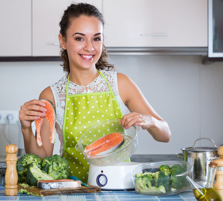 Happy housewife steaming salmon and vegetables in domestic kitchen
