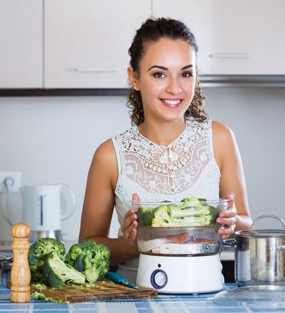 corcovado: Portrait of happy girl preparing fish and veggies in steamer Foto de archivo