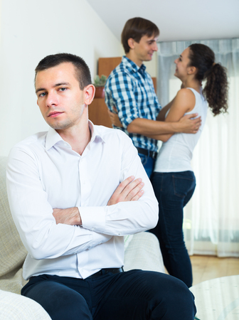 unrequited love: Unhappy man suffering from unrequited love: young woman prefers another guy Stock Photo