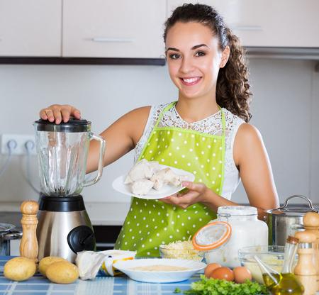 liquidiser: Happy young woman preparing chicken pate in domestic kitchen