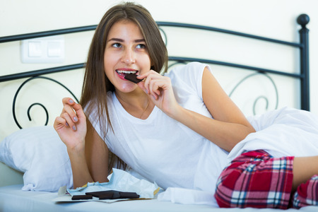 ordinary woman: Happy girl sitting in bed and eating dark chocolate indoors Stock Photo