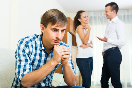 rival: Unrequited love in home interior: young woman prefers rival Stock Photo