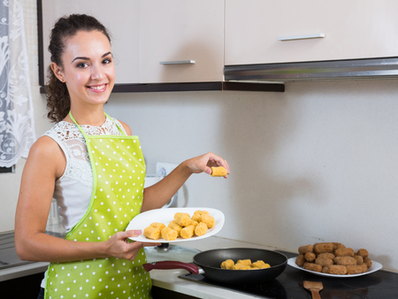 crocchette: Young woman frying filled croquettes in oil on stove Stock Photo