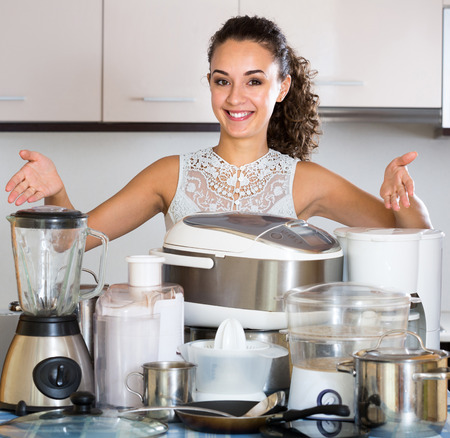 appliances: Happy girl posing with appliances at home kitchen Stock Photo