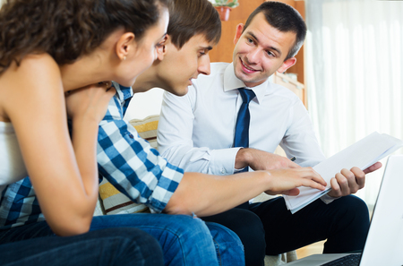 banking document: Young spouses and positive salesman with documents indoors