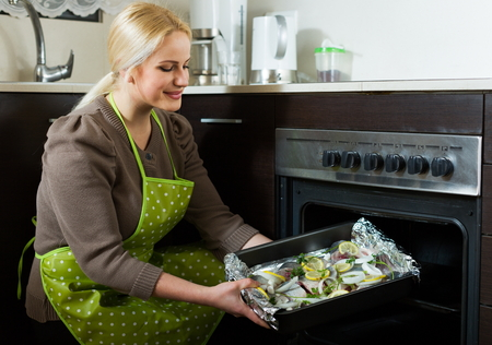 fryingpan: Blond woman cooking fish  in oven at home kitchen