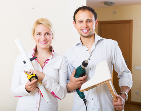 man power: Smiling young man and woman choosing place for shelf at home Stock Photo