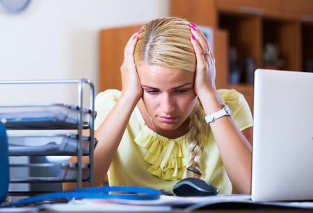 long depression: Tired blonde woman sitting at desk with laptop in office Stock Photo