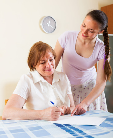 Two smiling women with financial documents at table in home or office interior