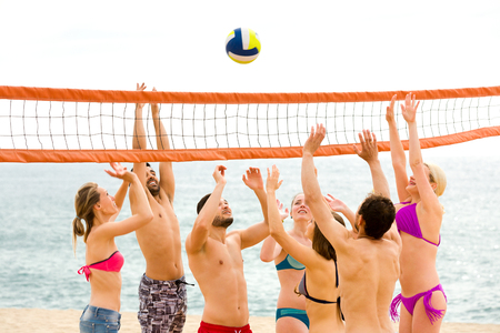 beach volley: Group of happy people playing beach volley during hot summer day