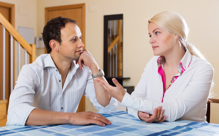 wistful: Casual young couple having serious conversation in living room
