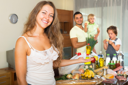 common market: Cheerful smiling family of four with bags of food at home. Focus on woman