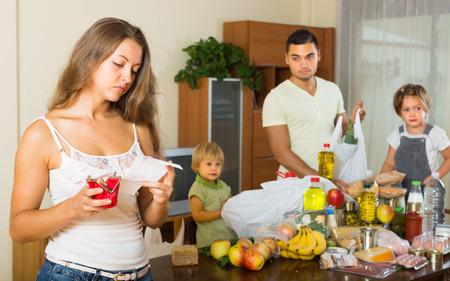problemas familiares: Pobre joven familia de cuatro con bolsas de alimentos en el hogar. Centrarse en la mujer Foto de archivo
