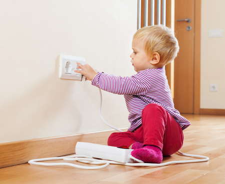 riskiness: Baby playing with electrical extension and outlet on floor at home Stock Photo