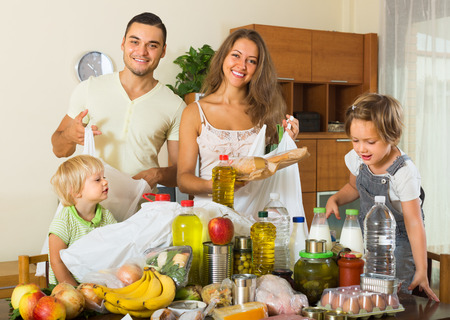 purchased: Smiling family with little children sorting purchased food out indoor. Focus on woman