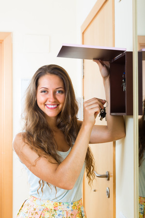 staying: Happy smiling woman with bunch of keys staying near house-keeper
