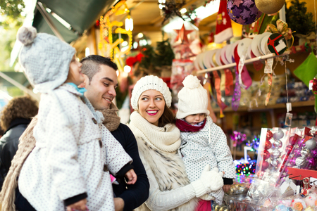 Happy family choosing Christmas decoration at Christmas market. Focus on woman and her daughter Stock Photo