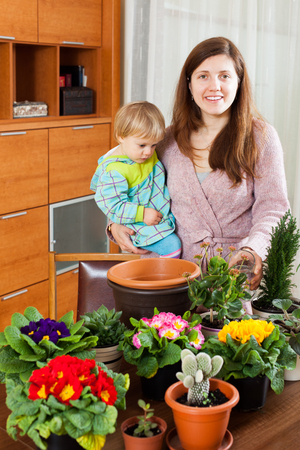 replant: Smiling female gardener with baby transplanting potted flowers at home