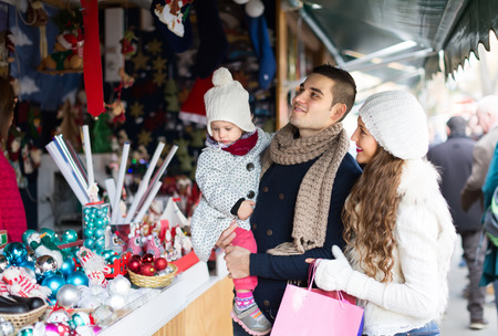young  family: Happy young family of three at Christmas market. Selective focus on man Stock Photo