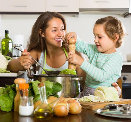 Madre joven positiva con la pequeña hija de cocina en cocina en casa