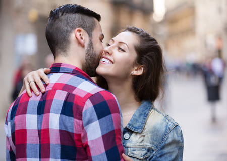 sidewalk talk: Happy young girl hugging her male friend outdoors Stock Photo