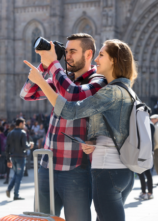 places of interest: Happy tourists in ordinary clothing seeing places of interest and taking photos with a dslr camera Stock Photo