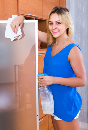 carefully: Ordinary happy girl in blue blouse dusting furniture indoors Stock Photo