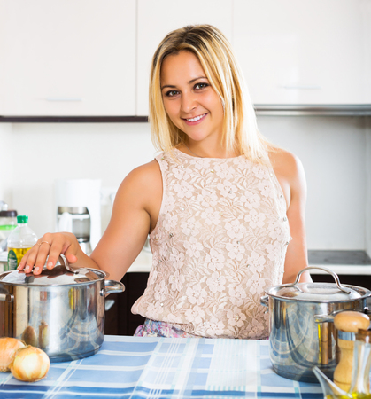 class maintenance: Young woman smiling at new kitchen